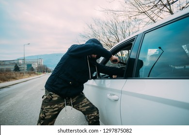 Carjacker aggressively attacking a car owner with a gun, trying to extort money.