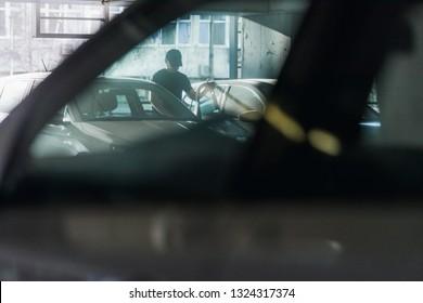 Carjacker is stealing a car successfully at parking lot