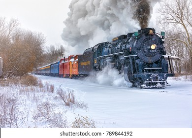 CARLAND, MICHIGAN,USA-DECEMBER 09: Steam engine Pere Marquette 1225 speeds along snowy railroad tracks, on December 9, 2017. The North Pole Express, carries holiday travelers between Owosso and Ashley