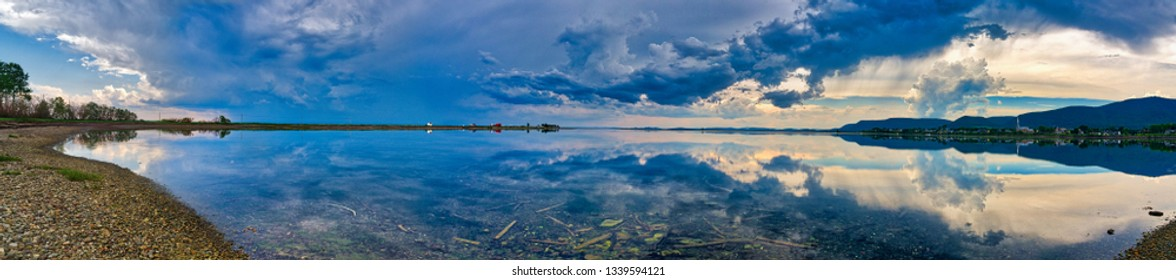 CARLETON QC/CANADA JUNE 29 2018 A panorama of an approaching summer storm perfectly reflected in the lagoon at Carleton in Gaspesie, Quebec, Canada