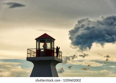 CARLETON QC/CANADA JUNE 29 2018 A man stood taking photos on the lighthouse at sunset in Carleton in Gaspesie, Quebec Canada