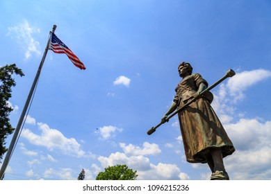 """Carlisle, PA, USA – June 26, 2016: The Mary Ludwig Hays - better known as Molly Pitcher - gravesite, located in the Old Graveyard Cemetery, includes a statue of """"Molly"""" standing alongside a cannon."""