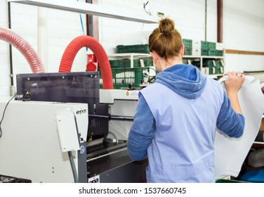 Carlos Barbosa / Rio Grande do Sul / Brasil - September 17, 2019: Woman working in interior of small clothes factory. Employee working among the machines and fabrics. Fashion industry.