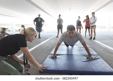 Carlos Vivanco, right, does push-ups during a recruiting boot camp at Las Vegas police headquarters in Las Vegas Saturday, June 25, 2016. Officer Stephanie Ward, left, supervises.