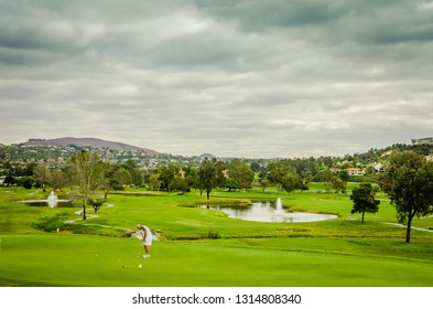 Carlsbad, CA / USA - 11-09-2014: A golfer puts on the green golf course despite gray clouds and imminent rain.