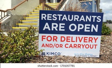 Carlsbad, CA / USA - April 11, 2020: A sign at the entrance to a shopping area reminds people that restaurants are still open for take out.