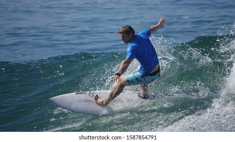 Carlsbad, CA / USA - August 24, 2019: Young man wearing a blue rash guard / sun protection shirt and graphic board shorts is surfing a wave.