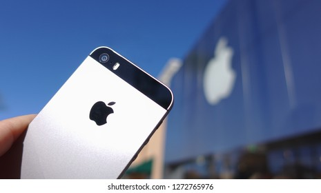 Carlsbad, CA / USA - January 2, 2019: Close up of iPhone SE held up in front of an Apple store in outdoor shopping mall