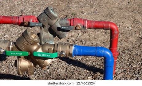 Carlsbad, CA / USA - January 4, 2019: valves with backflow preventer on red and blue water lines