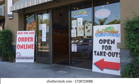 Carlsbad, CA / USA - May 11, 2020: Small restaurants advertise that they are still open for take-out and delivery with large signs.