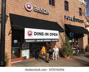 Carlsbad, CA USA - May 8, 2021: People are sitting under a huge sign advertising open dine in at the newly opened Panda Express in Bressi Village