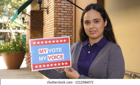 "Carlsbad, CA / USA - October 25, 2018: Hispanic voting concept - a pretty young woman of Mexican descent holds up a sign stating ""My Vote My Voice"""