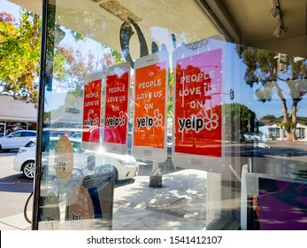 Carlsbad, California/United States - 10/08/2019: Several Yelp advertisement stickers attached to a retail store glass window
