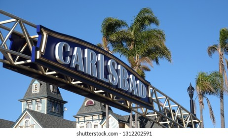 Carlsbad sign and palm trees in blue sky