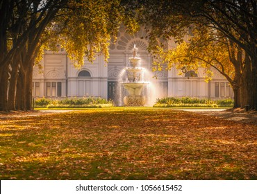 Carlton Gardens fountain and autumn trees catching the sunlight in front of the Royal Exhibition Building Melbourne, Victoria, Australia.