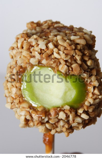 Carmel apple with nuts and a bite taken out of it.