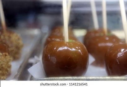 Carmel Apples. Fresh Made Carmel Apples with Peanuts on sticks on a shelf in a deli case for sale at a county fair.  Carmel Apples are a favorite treat world wide.