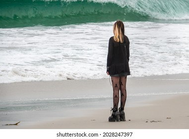 Carmel by the Sea, California - August 18, 2021: A young woman with streaked hair, black clothes and spiked boots enjoys the day at Carmel Beach as waves break in the background.
