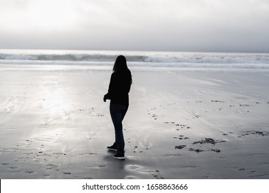 Carmel, California. Walking on the beach during sunset on a gloomy day. Staring into the ocean.
