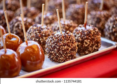 Carmel candied apples and chocolate chips and nuts coated apples on a stick