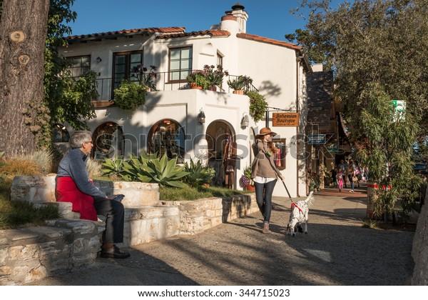 CARMEL-BY-THE-SEA, CALIFORNIA, UNITED STATES, November 28, 2015: A fashionably-dressed, tall and slender woman strolls down a sidewalk in Carmel on a November afternoon.