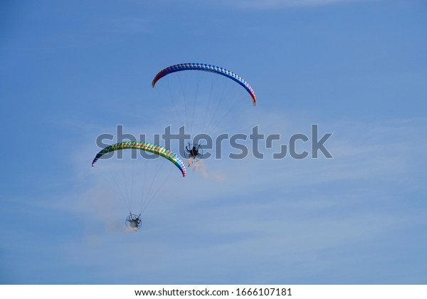 Carmona, Cavite, Philippines. March 6, 2020.  A hot air balloon festival features flying paragliders doing rounds for an admiring audience.