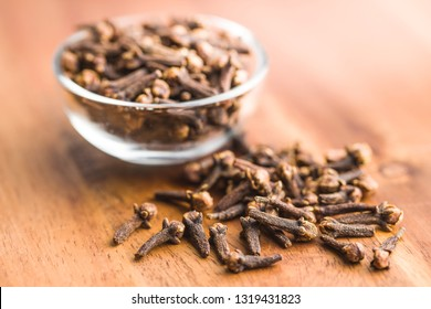 Carnation, dried clove spice on wooden table.