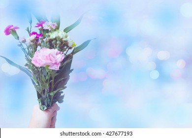 Carnation and flowers bouquet in hand holding with blur style sweet background bokeh