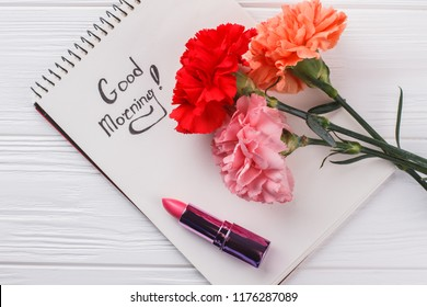 Carnation flowers, good morning wish and lipstic. White wooden background.