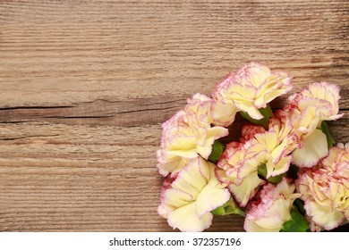 Carnation flowers on wooden background, copy space