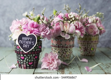 Carnation in mosaic flower pot with happy mother's day letter on heart wood
