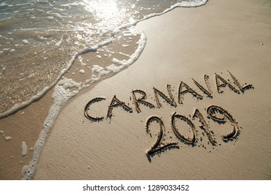 Carnaval 2019 message, spelled the Portuguese way, handwritten on smooth sand beach with wave in Rio de Janeiro, Brazil