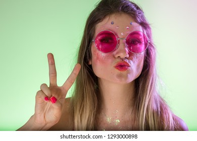 Carnaval Brazil. Hands and gesture. Face of young hippie woman with colorful makeup, dressed up for fun. Colorful background. Carnival concept, fun and party.