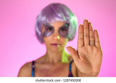 Carnaval Brazil. Hands and gesture: Stop, no harassment. Face of brazilian woman with violet wig and make up mask. Color background. Masquerade concept, celebration and festival.