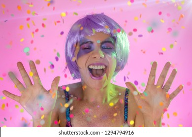 Carnaval Brazil. Surprised and excited. Color background. Masquerade concept, celebration and festival. Portrait of latin woman wearing purple wig and makeup mask.