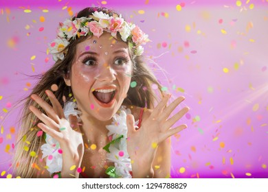 Carnaval Brazil. Surprised and excited. Throwing confetti. Colorful background. Carnival concept, fun and party. Face of young woman with colorful makeup, dressed up for fun.
