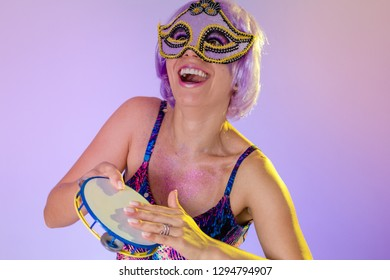 Carnaval Brazil Tambourine. Excited and Cheerful. Portrait of latin girl with violet wig and make up mask. Bright and Colorful. Holiday concept, tradition and costume.