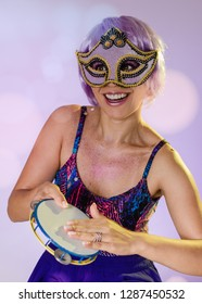 Carnaval Brazil Tambourine. Happiness and Joy. Portrait of latin girl with violet wig and make up mask. Color background. Masquerade concept, celebration and festival.