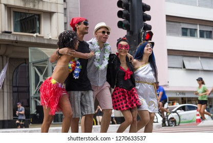 Carnaval party. Dressed group of Brazil people going to street Carnival. Happy brazilian revelers in costume celebrating in parade festival.