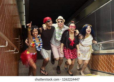 Carnaval party. Group of Brazil friends in costume celebrating carnival in the city. Dressed brazilian partygoers having fun in parade festival.