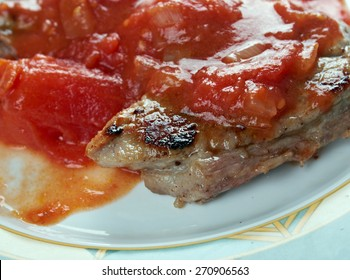 Carne pizzaiola - Neapolitan tradition that features meat. cooked with peppers, tomatoes and olive oil, long enough to tenderize the meat, garlic, tomato paste, oregano and basil.