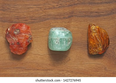 Carnelian, Beryl, Emerald, Amber. Collection of natural stones of minerals on a background of natural wood American black walnut. Beautiful untreated stones and minerals, crystals.