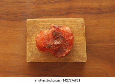 Carnelian raw untreated natural stone mineral, a collection of natural stones on a background of natural wood black walnut. A beautiful untreated stone. Flat lay.