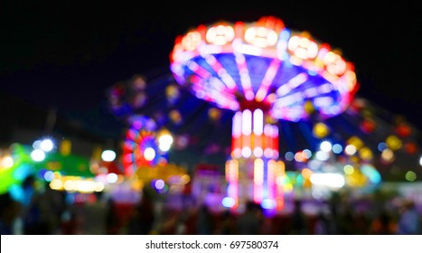 Carnival amusement park ride with swings. Spinning fair ride at night with bright purple red and yellow lights.