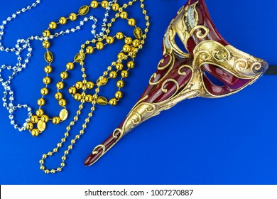 Carnival beautiful male venetian mask on blue background and colorful beads.