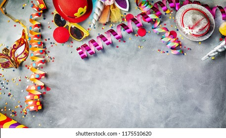 Carnival border of colorful streamers, confetti, hats, masks and sunglasses on grey with copy space for masquerade and party time