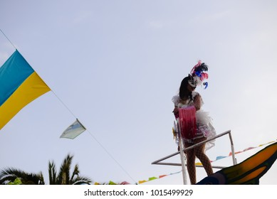 Carnival bright dancers. Joyful unrecognizable people celebrated festival in motion blur street outdoors background. Attractive happiness colorful beauty feathers glamour. Back side view photography