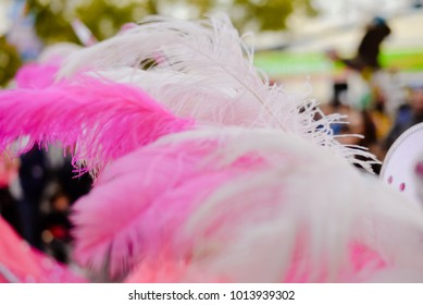 Carnival bright joyful unrecognizable people celebrated festival in motion blur street outdoors background. Attractive happiness colorful beauty feathers, glamour costumes. Back side view photography