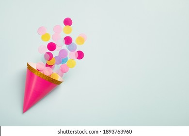 Carnival cap with colorful paper confetti on light blue background. Birthday party, carnival or anniversary card. Top view, flat lay, copy space