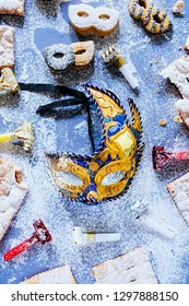 Carnival concept, elegant golden blue mask  circled by cookies and sweeties typical of carnival, like italian sfrappole or Chiacchiere, carnival fried pastry,flatly with lot of pastry sugar.